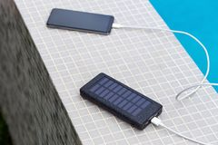 Solar smartphone charger charging phone at swimming pool Stock Photos
