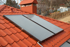 Solar system on the roof. Solar water heating system on the red roof. Gelio panels stock photo