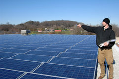 Solar tech. A technician at work pointing across a blue field of solar panels Royalty Free Stock Images