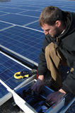 Solar tech. A technician at work testing a blue of solar panels Royalty Free Stock Photo