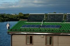 Solar water heater and battery. Wind turbine on the roof Stock Photo
