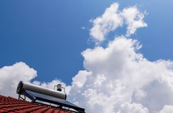 Solar water heater boiler on red rooftop, beautiful blue sky with white clouds. Space for text royalty free stock image