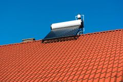 Solar water heater boiler on residentual house rooftop. Perfect blue sky background stock image