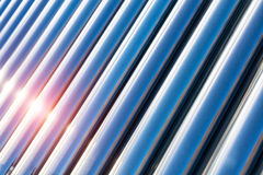 Solar water heater closeup. Sunlight on blue vacuum tubes royalty free stock images