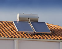 Solar water heater on roof of house. Solar water heater on roof of tile roofed house Royalty Free Stock Photos
