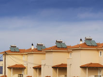 Solar water heaters. Solar water heater on roof of tile roofed house Royalty Free Stock Photos