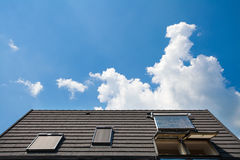 Solar water panel with dormers on a roof against blue sky. Royalty Free Stock Image