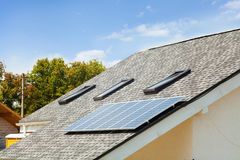 Solar water panel heating on new house roof with skylights against blue sky. Royalty Free Stock Photos
