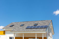 Solar water panel heating on new house roof with skylights against blue sky. Stock Photo