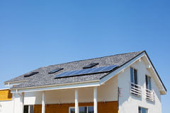 Solar water panel heating on new house roof with skylights against blue sky. Stock Images