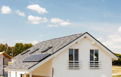 Solar water panel heating on new house roof with skylights against blue sky. Royalty Free Stock Photography
