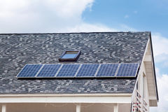 Solar water panel heating on new house roof with skylights against blue sky. Royalty Free Stock Images