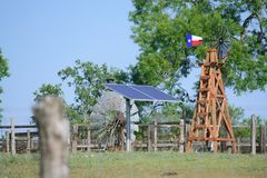 Solar Water well with Texas Windmill in front of summer green trees, farm ranch fence and blue sky background Royalty Free Stock Images