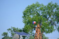 Solar Water well with Texas Windmill in front of summer green trees, farm ranch fence and blue sky background Stock Images