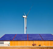 Solar and wind energy. Solar panel on a farm building with a wind mill in the background Stock Image