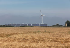 Solar and wind energy on a farm. Soalr and wind energy on a farm with corn on the foreground Stock Images