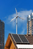 Solar and wind energy generators on wooden house. Solar panels on a roof of wooden house with white banner for your text and wind generator opposite of modern Stock Photo