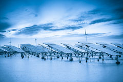 Solar and wind power in coastal mud flat Royalty Free Stock Photo