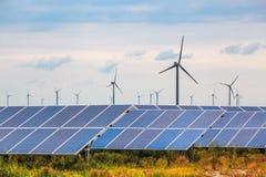 Solar and wind power in coastal mud flat. Renewable energy background Royalty Free Stock Photo
