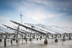 Solar and wind power in coastal mud flat Stock Photos