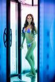 Solarium Beeld van het glimlachen vrouw het stellen in bikini stock fotografie