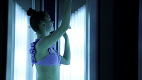 solarium Härlig ung flicka i en purpurfärgad baddräkt som ska garvas i den vertikala solariet arkivfilmer