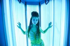 Solarium Menina bonita com tranças africanas em um vestido para danças orientais que toma sol em um vertical sunbed Fulgor de néo foto de stock royalty free