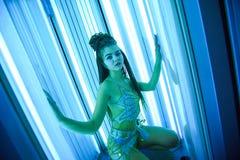 solarium Nätt flicka med afrikanska flätade trådar i en klänning för orientaliska danser som solbadar i sunbed ett vertikalt Blåt royaltyfria bilder