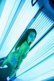 solarium Nätt flicka med afrikanska flätade trådar i en klänning för orientaliska danser som solbadar i sunbed ett vertikalt Blåt royaltyfri foto