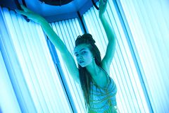 Solarium. Pretty girl with african braids in a dress for oriental dances sunbathing in a vertical sunbed. Blue neon glow stock photography