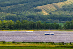Solarkraftwerk auf einem Hintergrund von grünen Hügeln Stockbild