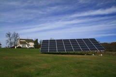 Solarrasterfeld, das ein neues Haus anschält Lizenzfreie Stockbilder