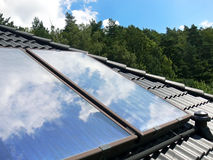 Solars and sky. Close up of the black tiled roof and new solar panels with blue sky and clouds reflection Royalty Free Stock Images
