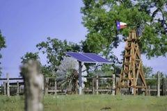 Solarwasser gut mit Texas Windmill vor Sommergrünbäumen, Bauernhofranchzaun und Hintergrund des blauen Himmels lizenzfreie abbildung