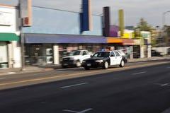 Solas luces del coche policía que van abajo de la calle Imagen de archivo