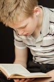 Solas sentada y lectura del muchacho un libro fotos de archivo