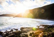 Solbörjan som ska ställas in över en strand Fotografering för Bildbyråer