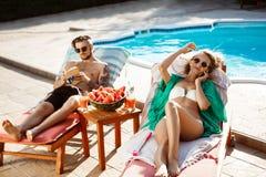 Solbada för vänner som ligger nära simbassäng tala för flickatelefon Fotografering för Bildbyråer