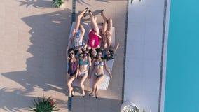 Solbada, lyckliga vänflickor in i baddräkten och solglasögon som kopplar av på dagdrivare nära Poolside på lyxig ferie stock video