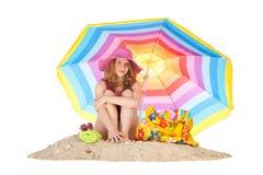 Solbada på stranden med den färgrika slags solskydd royaltyfri bild
