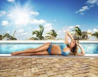 Solbadar på poolside Arkivfoto