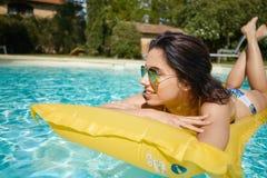 Solbadning för ung kvinna i simbassäng för brunnsortsemesterort royaltyfria bilder