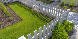 Solbelyst gård med det vita staketet och buskar för gräsmatta royaltyfria foton