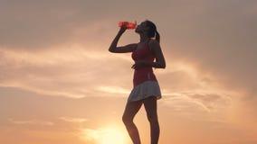 Solbelyst landskap med en ursnygg ung dam som dricker från en flaska lager videofilmer