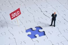 Sold. Business man with puzzle and sold sign stock photos