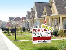 Sold. View of a residential street and a real estate for sale sign in the foreground with a prominent SOLD notice stock image