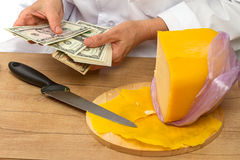 Sold cheese counts money Royalty Free Stock Images