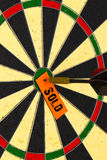 Sold. Darts with dart which was pinned a sheet of paper for labe Royalty Free Stock Photo