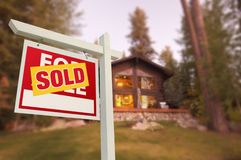 Sold Home For Sale Sign and Beautiful Log Cabin Stock Photo