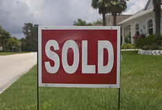 Sold House Sign. Red and white sold sign for difused house in background, green lawn, palm trees stock photo